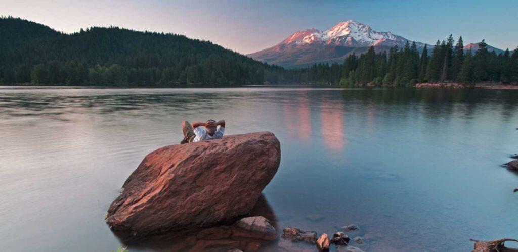 Man with backwards baseball cap sitting on a boulder on Lake Siskiyou looking at Mt. Shasta