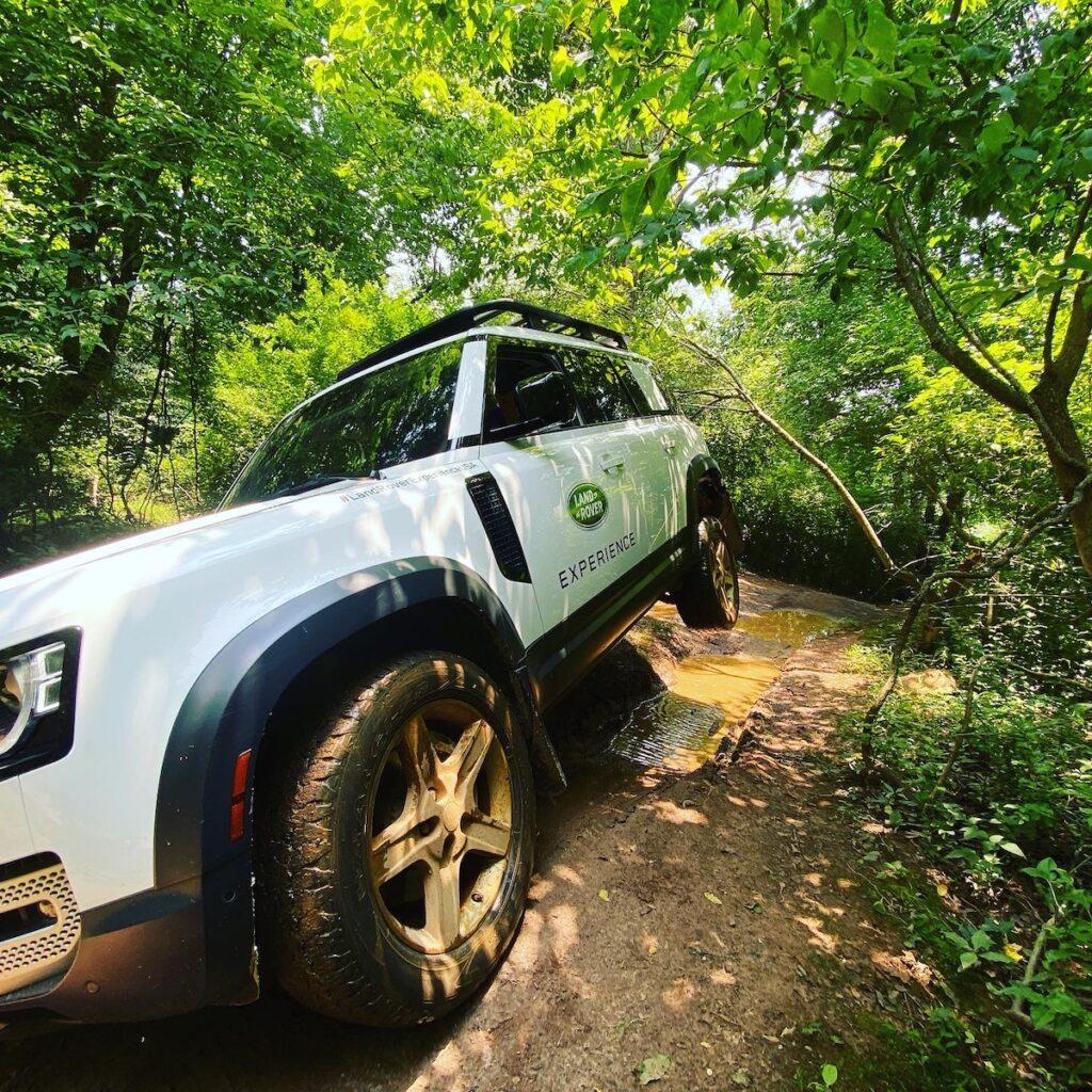 White land rover drives through muddy dirt road.