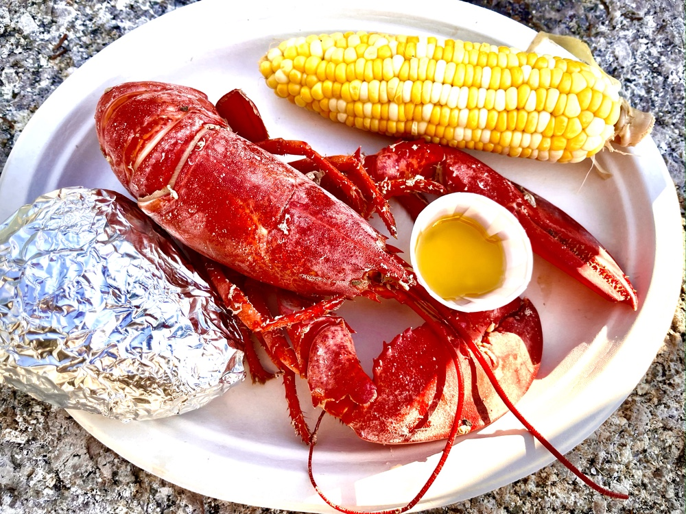 A Traditional Lobster Dinner With Potato And Corn