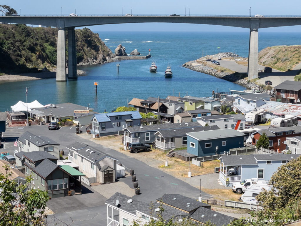Harbor with bridge in background looking down on modular homes and restaurant