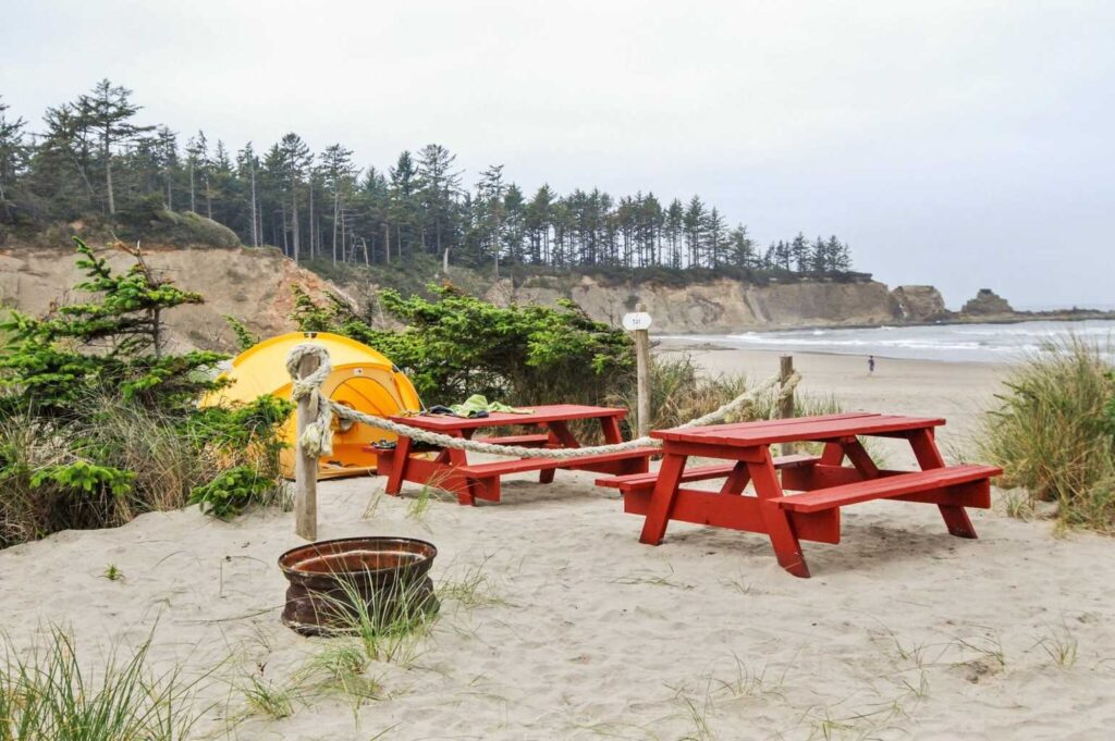 Oceanside RV Resort and Campground waterside tent campsite with two red picnic tables and a fire pit.