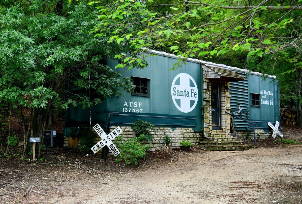 Renovated Santa Fe Covered Wagon nestled in the woods with a log cabin at the Country Woods Inn, Glen Rose.