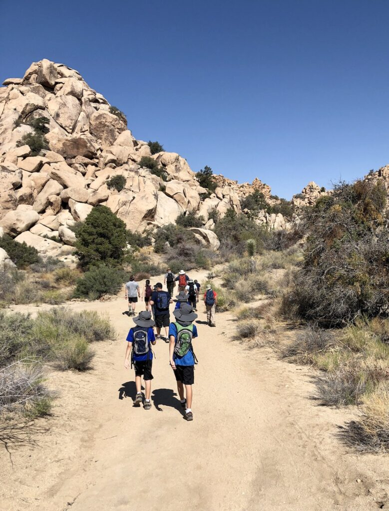Ranch tour group hikes up hill.