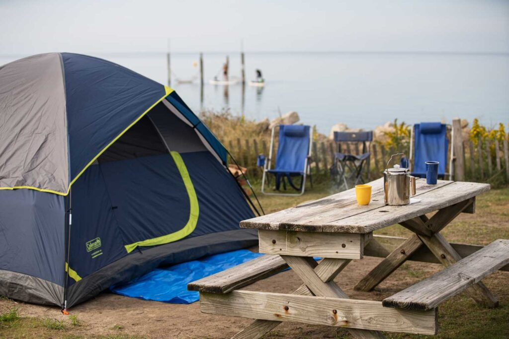 waterfront tent camping at Rodanthe Watersports and Campground in North Carolina. Picnic table with coffee, paddleboarders in background.