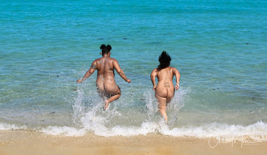 Two women running into water to skinny dip.