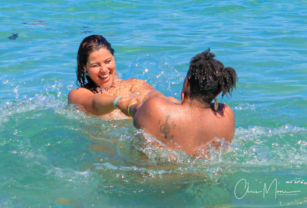 Two women splashing in the water.
