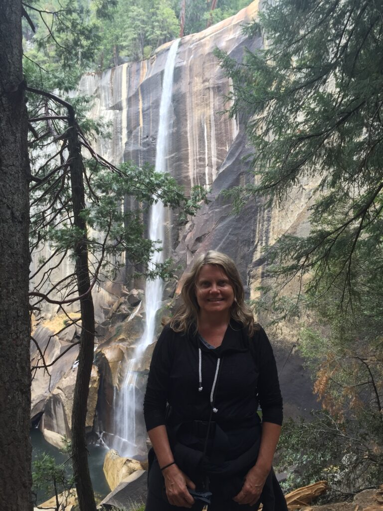 Woman sits in front of Vernal Falls On The Mist Trail in Yosemite National Park.
