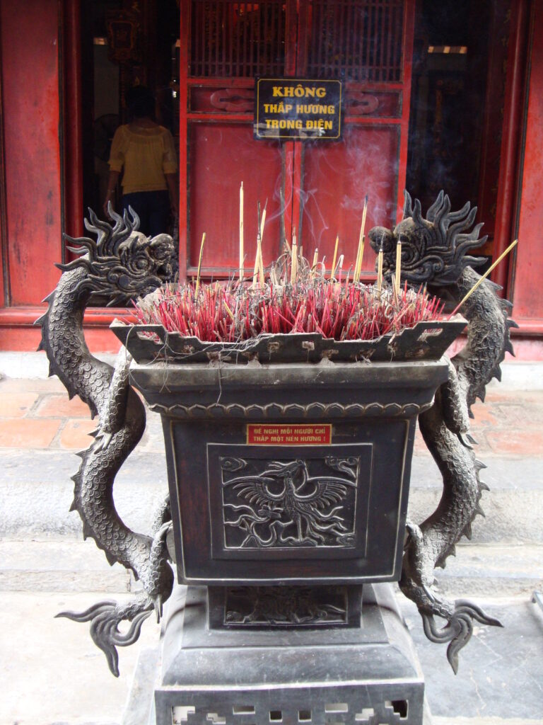 Dragons on Vietnamese incense pot with incense burning.