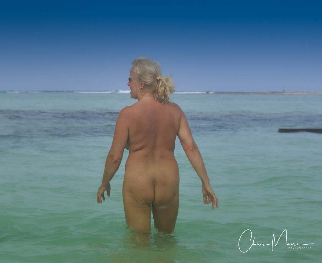 Woman walking into water nude.