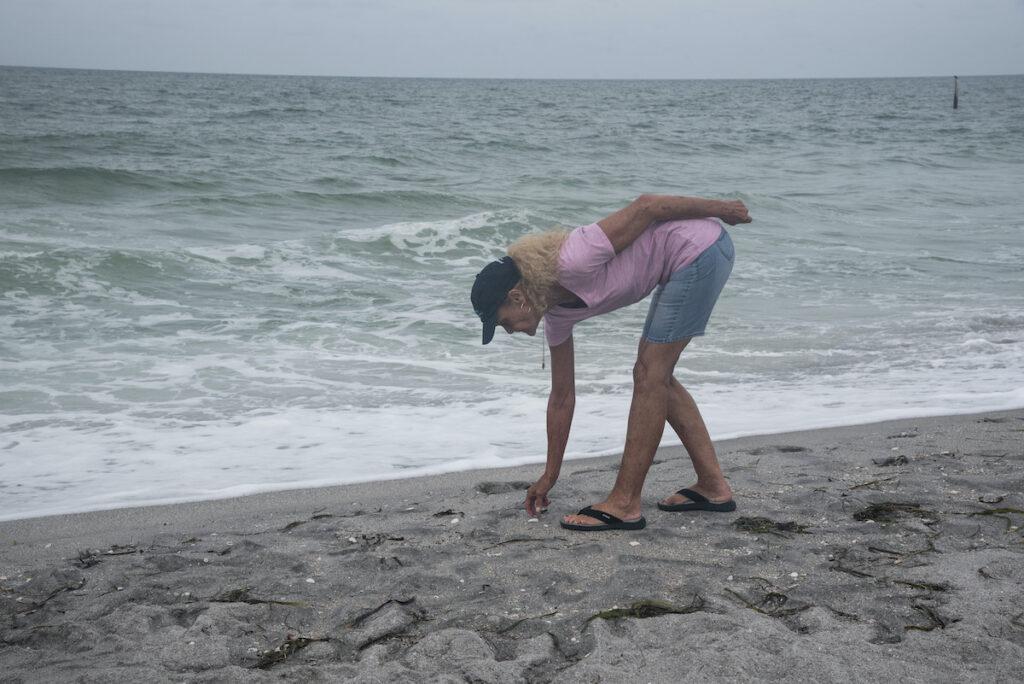 Woman hunts for shark teeth at Venice Beach, FL.