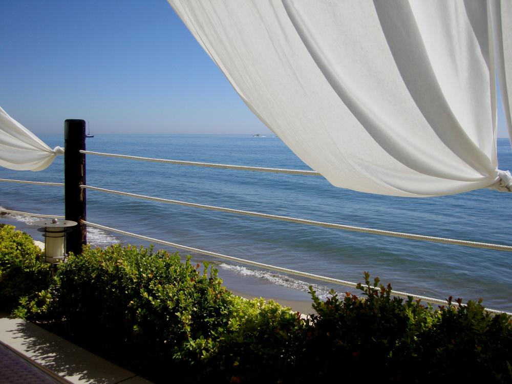 A flowing white curtain of a beach cabana in a luxury seaside club overlooking blue Mediterranean, Marbella, Spain