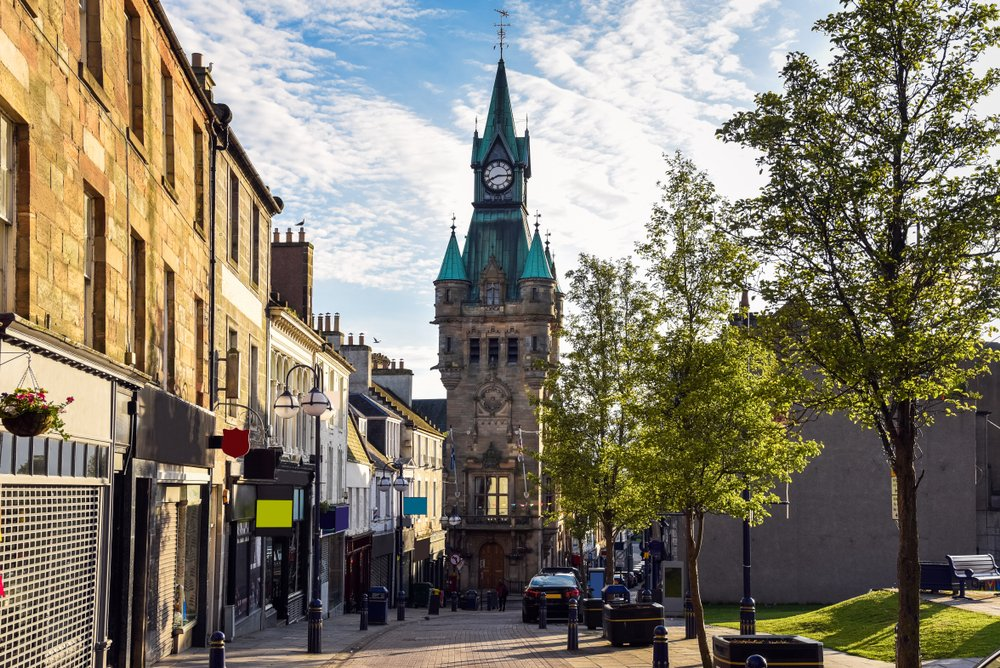 Traditional architecture with shops and restaurants along a pedestrian street in a town centre at sunset. Dunfermline, Fife, Scotland, UK.