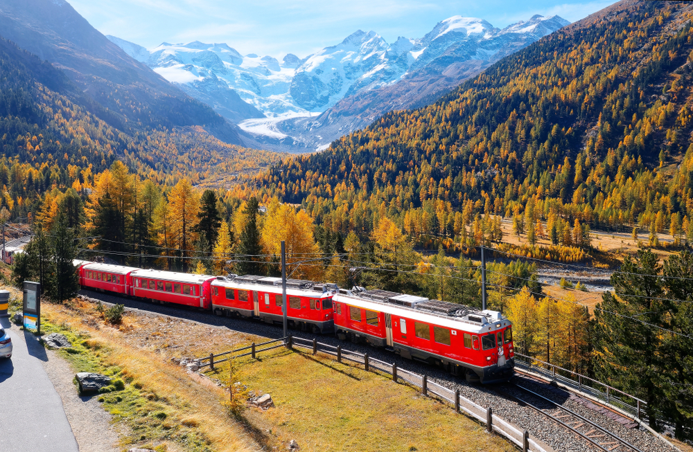 A local train travels thru fall colors at Montebello Curve on a brisk autumn day with Morteratsch glacier lying below Piz Bernina & snow-capped alpine mountains in background in Pontresina Switzerland