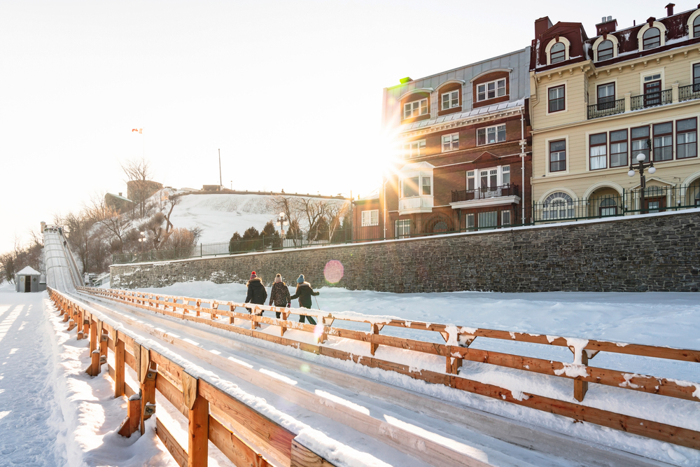 Quebec, Canada - January 17, 2020: Terrasse Dufferin slide on Dufferin terrace with Chateau Frontenac on a snowy day, popular winter outdoor activity, a famous landmark in Old Quebec City, Canada.