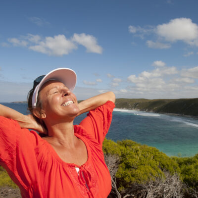 happy middle aged woman on cliff overlooking ocean