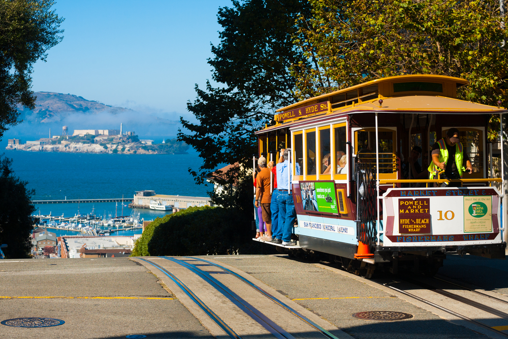 2011: Powell Hyde cable car, an iconic tourist attraction, descending a steep hill peak overlooking Alcatraz prison island and the bay