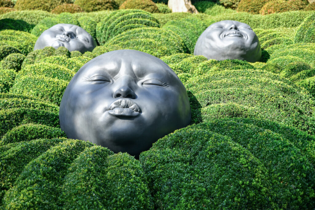 Des têtes géantes en caoutchouc dorment sur des oreillers verts.  Jardin de buis dans le célèbre jardin d'Etretat, Normandie, France.