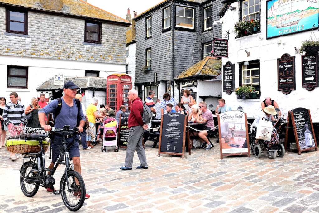 Diners eating and drinking alfresco at the Sloop Inn on the quayside at St. Ives in Cornwall.