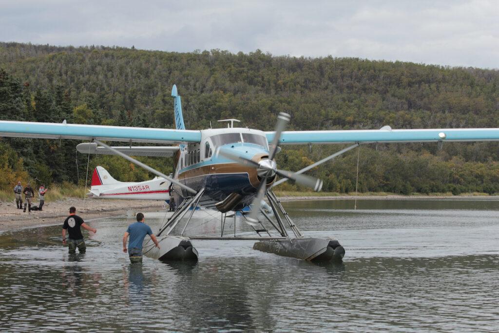 Men preparing Katmai air float plane for take off at the Katmai National Park.