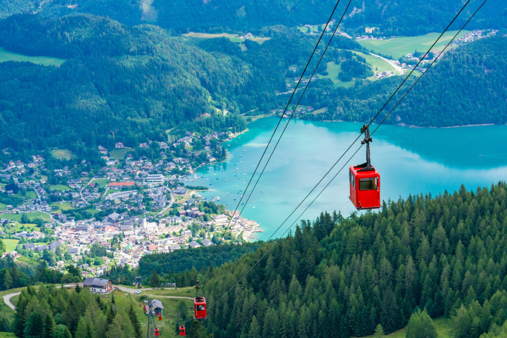 View of the village of St.Gilgen, Lake Wolfgangsee and the red gondolas of the Seilbahn cable car from the Zwolferhorn mountain in the Salzkammergut region, Austria.