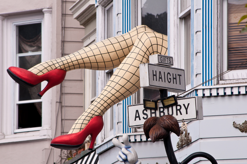 Iconic fishnet stockinged legs with red heels hanging out of a window on Haight Ashbury in San Francisco