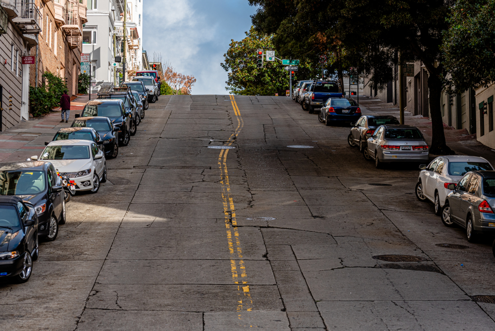 2016. Photo looking up to the top of a very hilly street with cars parked in all the available parking spaces in San Francisco, CA