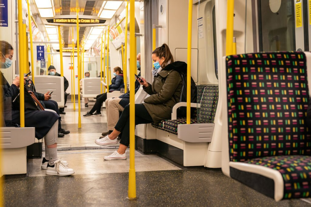 Passengers in a London Underground Tube train during rush hour using mobile telephones to text during the COVID Coronavirus pandemic in London, Englan