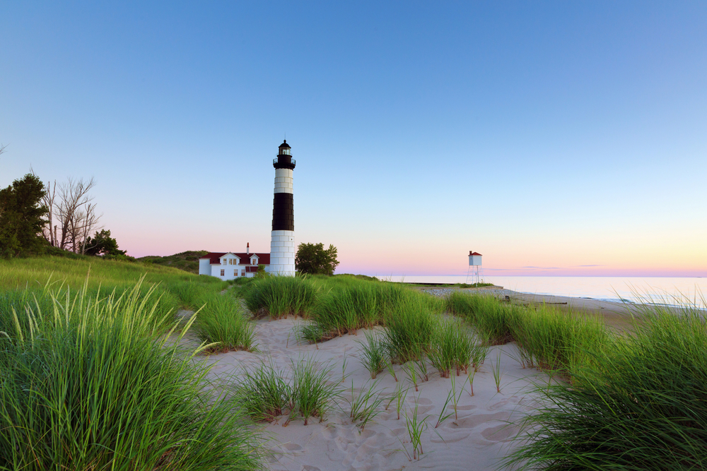 Big Sable Point Lighthouse in Ludington State Park on a Lake Michigan beach. Sunset hues in the background.