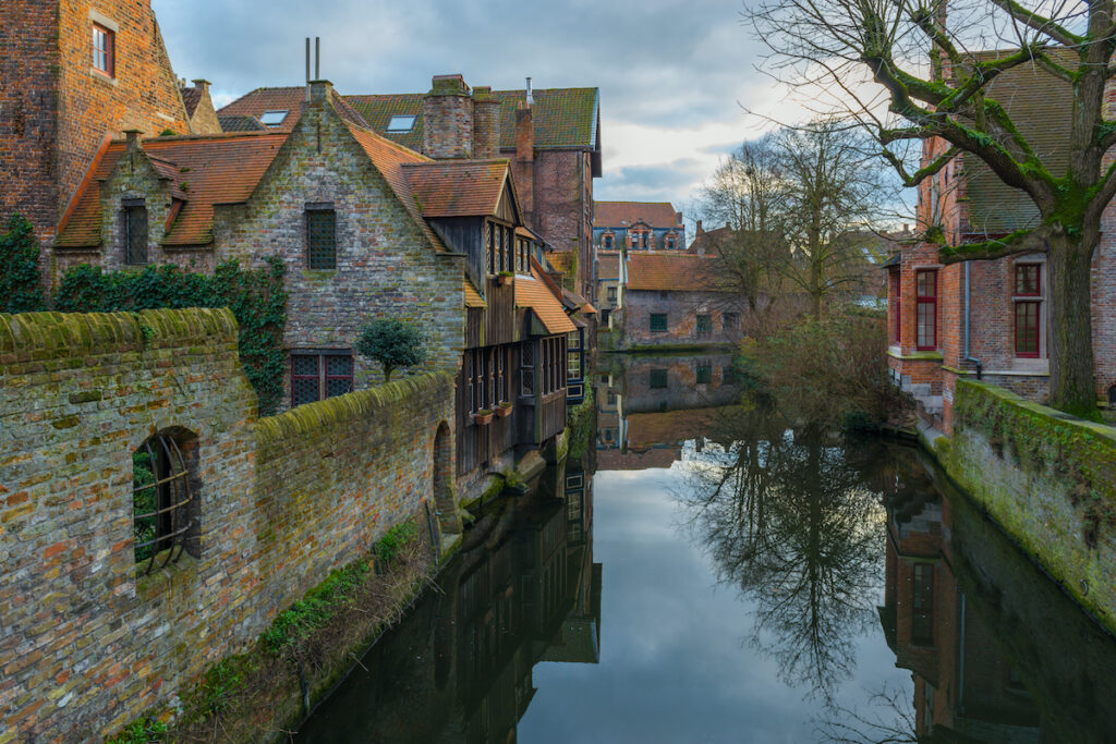 Canal and traditional medieval housing in the historic city center of Bruges at sunset, Belgium.
