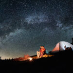 couple camping in tent at night under the stars