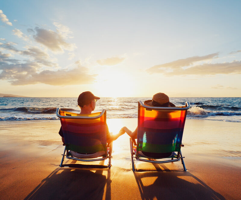 retired couple relaxing on beach during sunset