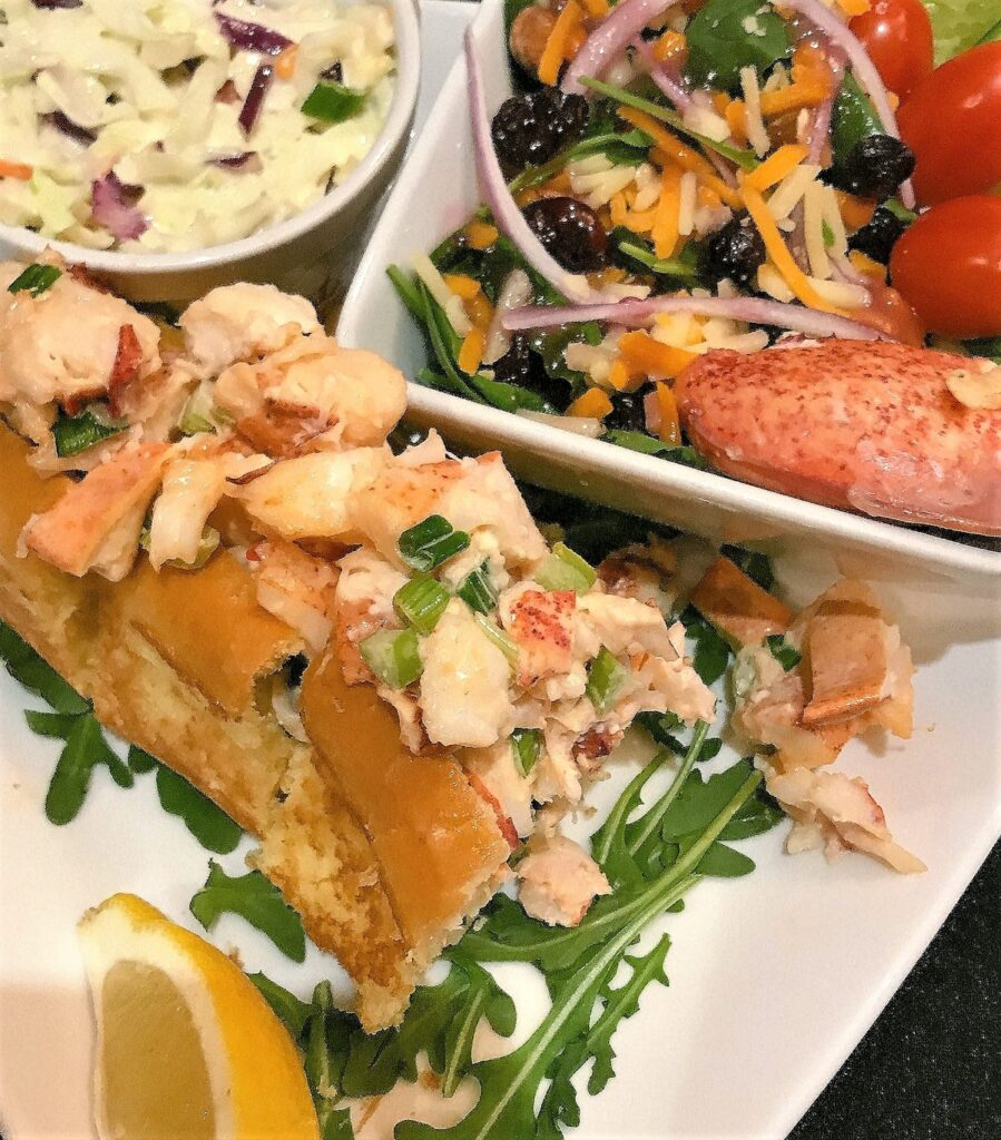 Lobster roll with salad and coleslaw.