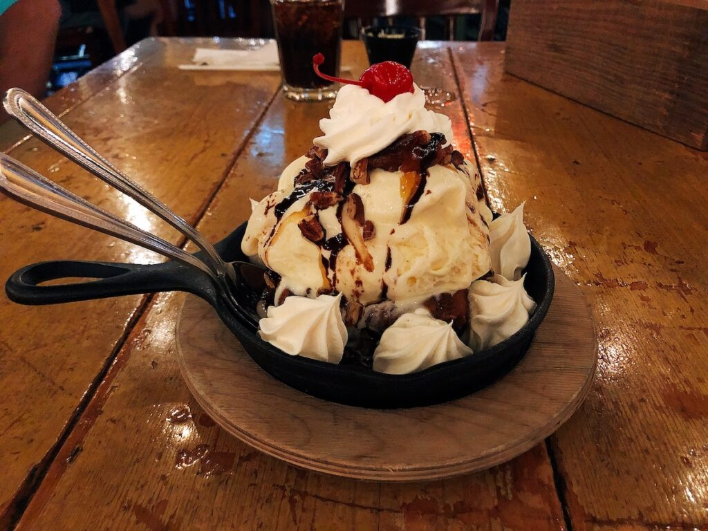 Big ice cream with whipped cream and cherry on top served in a small cast iron skillet.