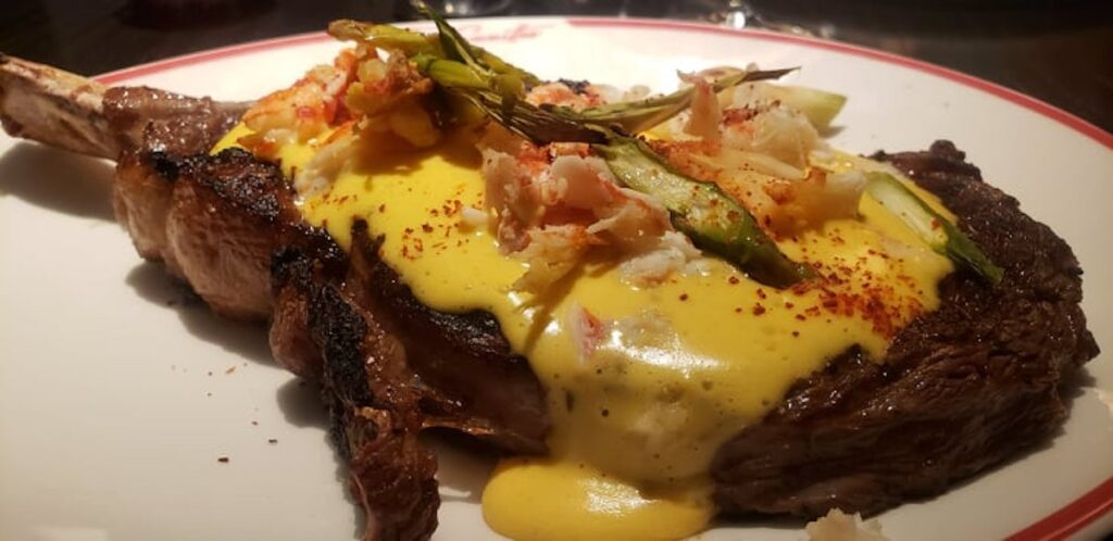 The cowboy cut steak with cheese on top at The Committee Chophouse.