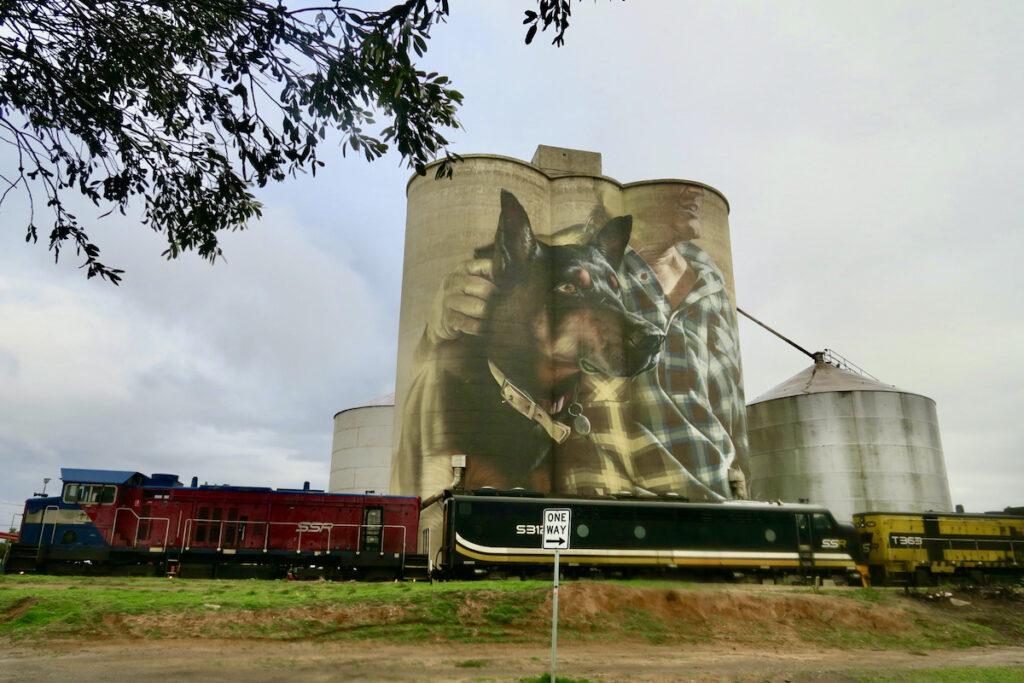 Farmer and dog silo art with train