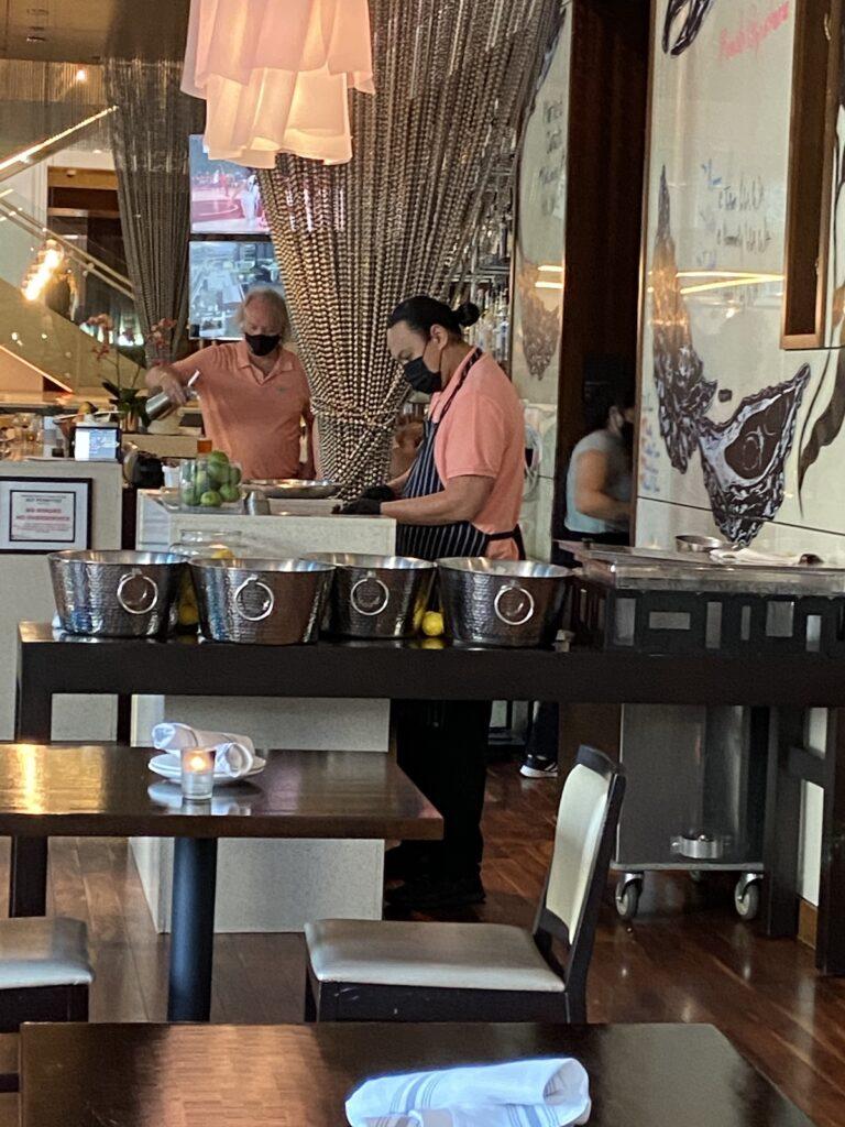 Waiters work behind the bar at Tidal + Dining at Hyatt At Olive 8.