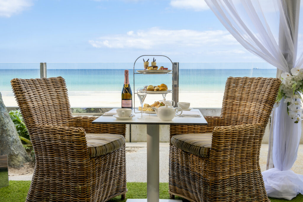 Champagne, tea and sweet scones sitting on table at Carbis Bay Estate overlooking the ocean.
