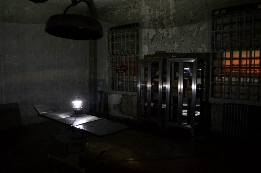 Black and white photograph of inside Alcatraz. Fiery orange sunset over San Francisco Bay can be seen through window.