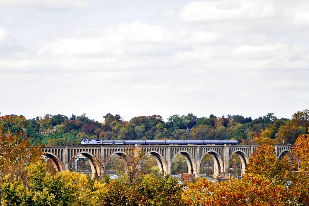 Amtrak train going across the Cardinal James River Bridge fall foliage