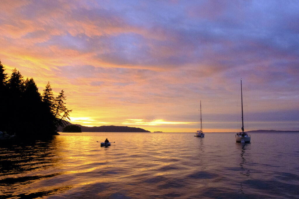 Sail boats, close to shoreline, float peacefully upon the water while the sun goes down.