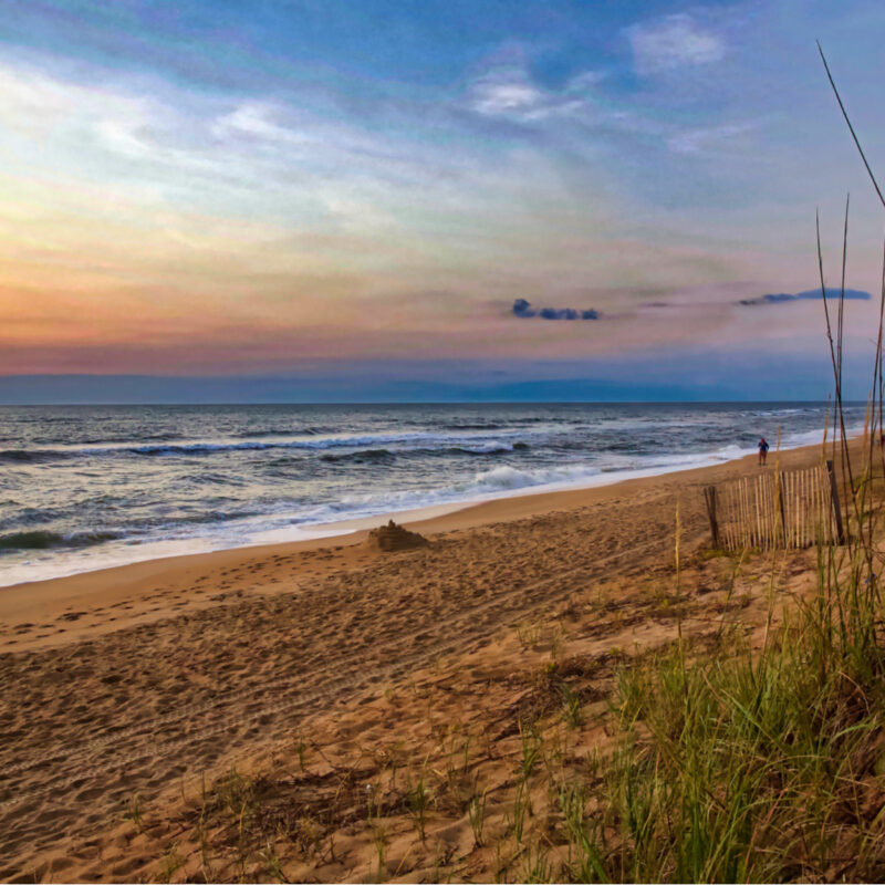 Colorful sunrise on a North Carolina beach, waves breaking on a sandy shore framed by dune grass. Duck, NC