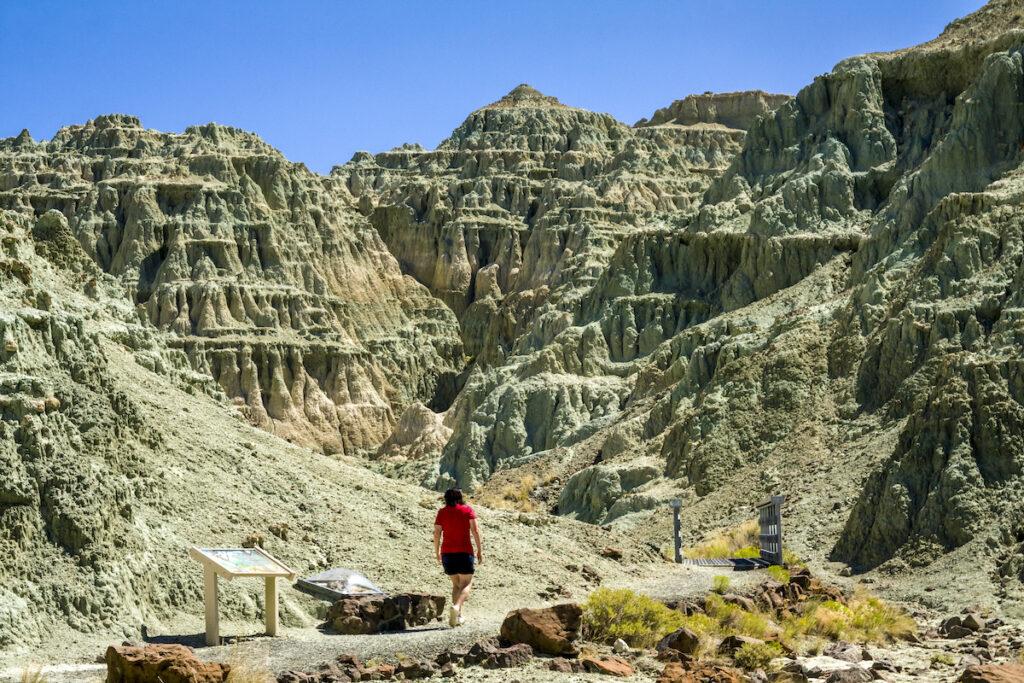 Woman walks through rouged dessert like mountain terrain.
