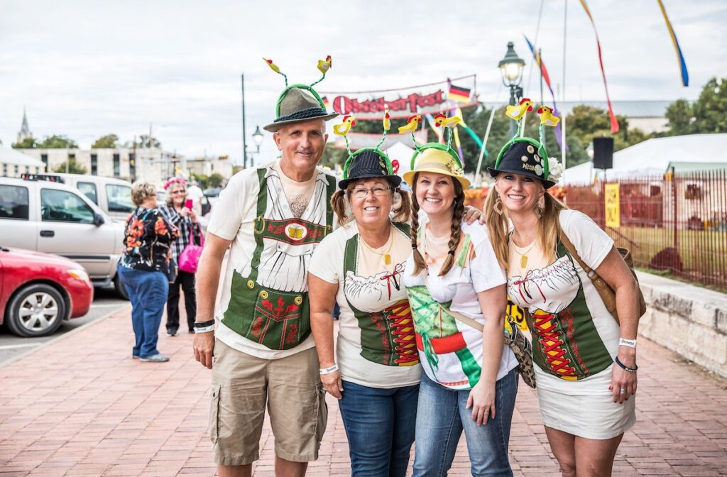 Group of visitors of Octoberfest, stand in german costume in front the entrance.