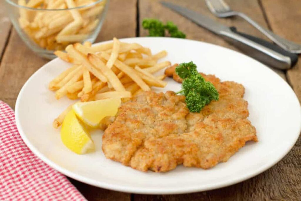 Plate of Schnitzel with french fries and lemon wedge.