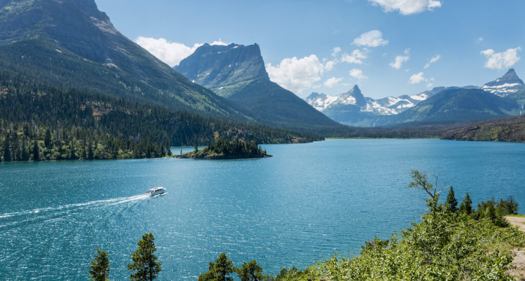 From a distance a boat travels along a turquoise blue lake with snowcapped mountains.