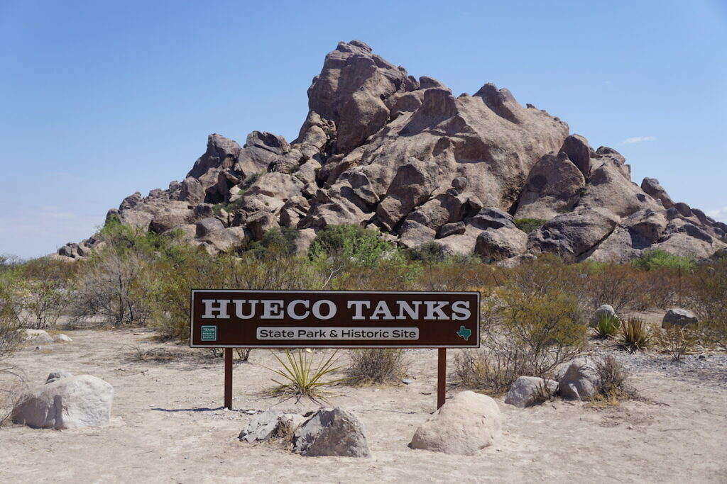 Another Hueco Tanks sign for the State Park and Historic Site Entrance with giant rock formation in the background.
