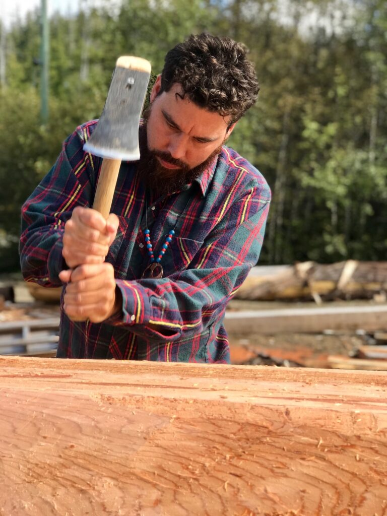 Man chops wood at the Kiamichi Owachito Festival of the Forest in Broken Bow, Oklahoma.