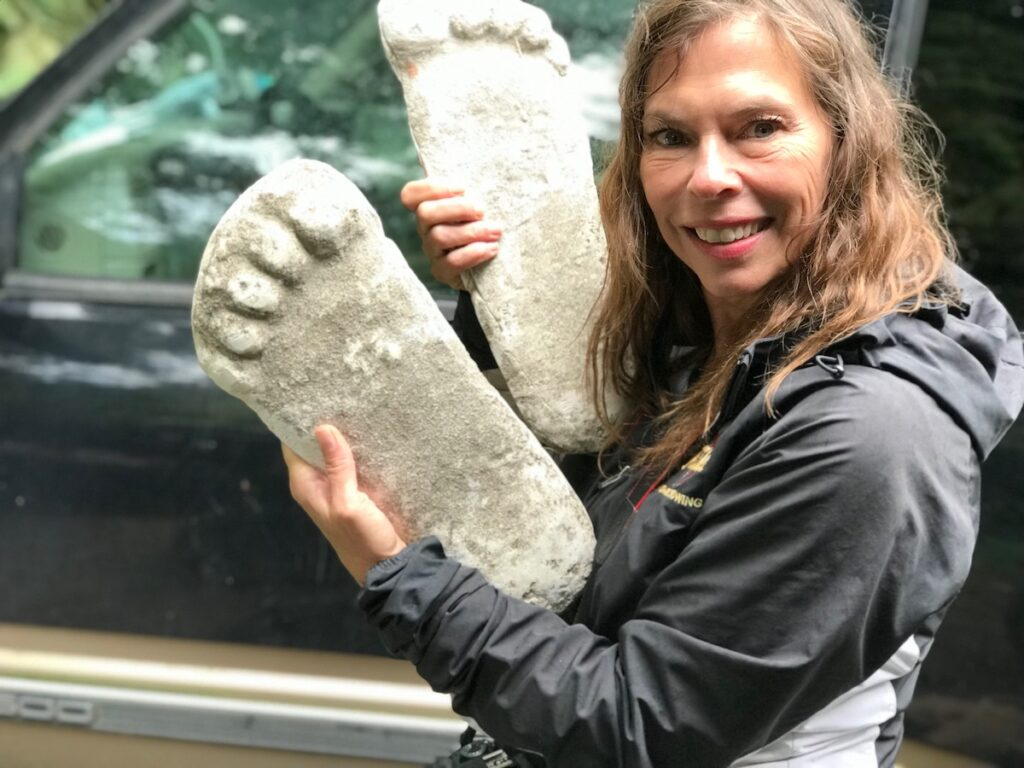 Woman holds molds of Big Foot's feet at the Bigfoot Festival in Honobia, Oklahoma.