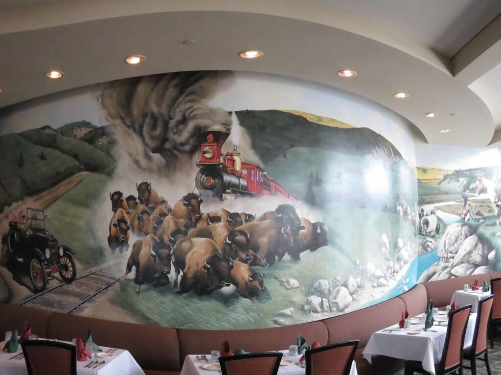 Mural of steam engine, wild buffalo covered wagons and car in the dinning room of Dusters steakhouse.