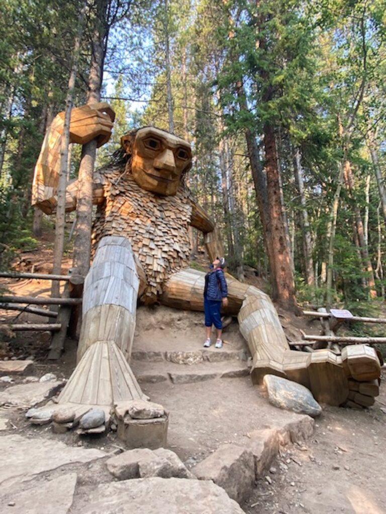 "Woman stands next to ""The Breckenridge Troll"", 15-foot tall wooden troll sculpture located on the Trollstigen Trail in Breckenridge."
